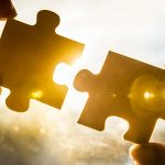 Two people working together to put puzzle pieces together